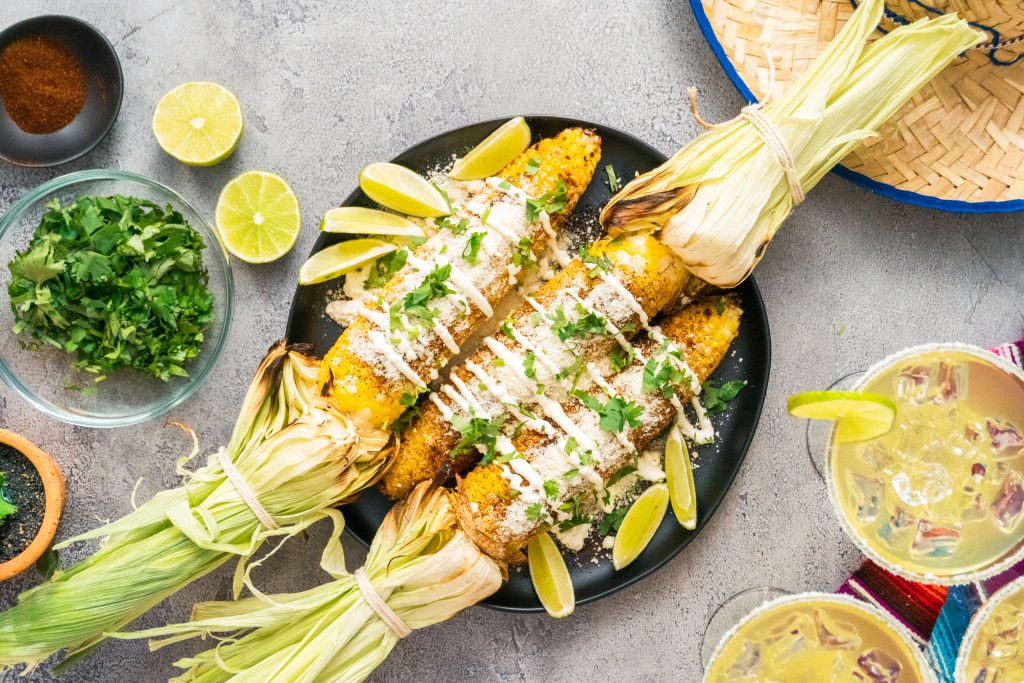 Grilled Elote - Mexican street corn with cheese, chili pepper, garlic and cilantro. top view.