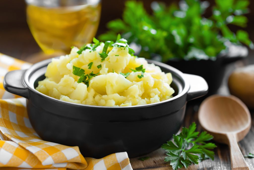 Creamy mashed potatoes are made with cream cheese and garnished with chives and parsley.